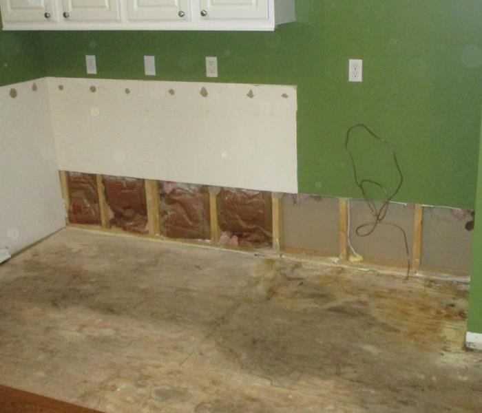 Water Damaged kitchen with exposed sub floor, drywall on perimeter is missing and insulation behind drywall is missing
