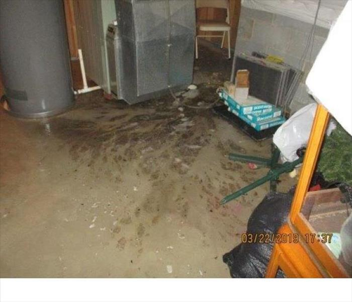 Basement utility room with concrete flood covered with water containing raw sewage