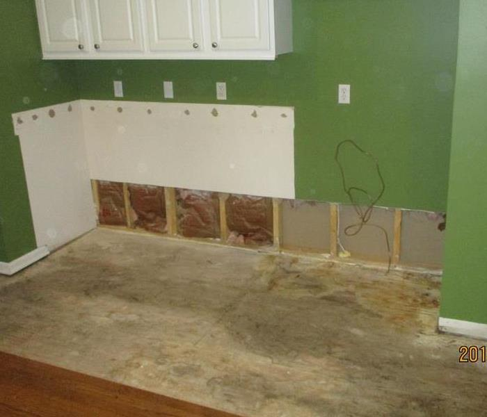 A green kitchen with white cabinets and medium brown color luxury vinyl flooring that suffered water damage .